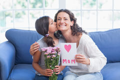Fleurs de offre et carte de fille mignonne à sa mère photographie stock libre de droits