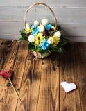 Fleurs de panier avec le coeur rouge et blanc sur un fond en bois Image libre de droits