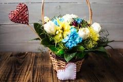 Fleurs de panier avec le coeur rouge et blanc sur un fond en bois Images libres de droits