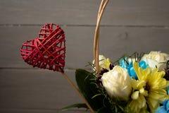 Fleurs de panier avec le coeur rouge sur un fond en bois Photographie stock libre de droits