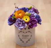 Fleurs de papier colorées dans un petit seau blanc Photo stock