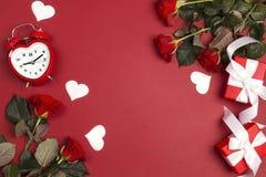 Fleurs de Rose avec le réveil, les cadeaux et les coeurs décoratifs sur le fond rouge Concept de jour de valentines de St images stock