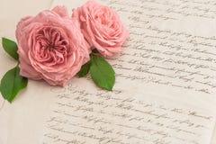 Fleurs de rose de rose au-dessus de lettre manuscrite antique Photographie stock libre de droits