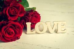 Fleurs de roses rouges avec le mot en bois AMOUR Images stock
