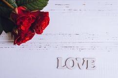 Fleurs de roses rouges avec le mot en bois AMOUR Images libres de droits