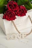 Fleurs de roses rouges avec le mot en bois AMOUR Photos stock