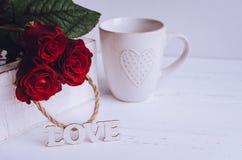 Fleurs de roses rouges avec le mot en bois AMOUR Photo libre de droits