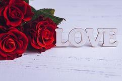 Fleurs de roses rouges avec le mot en bois AMOUR Photo stock