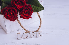 Fleurs de roses rouges avec le mot en bois AMOUR Photographie stock libre de droits