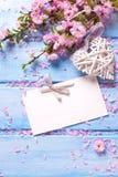 Fleurs de Sakura, coeur décoratif et Empty tag sur b en bois bleu Photo stock