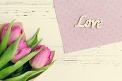 Fleurs de tulipe avec le mot en bois AMOUR Photo stock