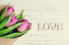 Fleurs de tulipe avec le mot en bois AMOUR Images libres de droits