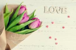 Fleurs de tulipe avec le mot en bois AMOUR Photographie stock libre de droits