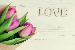 Fleurs de tulipe avec le mot en bois AMOUR Photos libres de droits