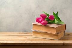Fleurs de tulipe et livres de vintage sur la table en bois Photo libre de droits