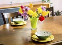 Fleurs de tulipes, de narcisse et de lilas dans un vase en verre vert sur une table en bois Disposition de Tableau Photographie stock libre de droits