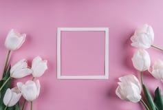 Fleurs de tulipes et feuille de papier blanches au-dessus de fond rose-clair Cadre ou fond de jour de valentines de saint image stock