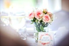 Fleurs des roses sur la table de mariage avec la carte, le fond rose romantique pour la partie ou l'événement Image libre de droits