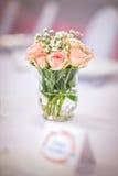 Fleurs des roses sur la table de mariage avec la carte, le fond rose romantique pour la partie ou l'événement Photographie stock libre de droits