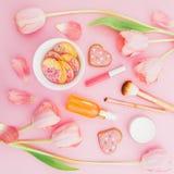 Fleurs en pastel de tulipes, cosmétiques avec l'arome et biscuits doux sur le fond rose Configuration plate, vue supérieure Photographie stock libre de droits
