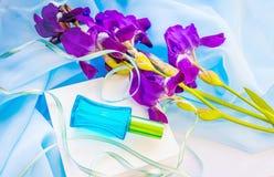 Fleurs en verre bleues de bouteille et d'iris de parfum Images stock