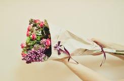 Fleurs enveloppées en papier dans des mains Photos stock