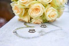 Fleurs et anneaux de mariage sur la surface gelée Photos libres de droits