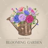 Fleurs et bidon d'arrosage Image stock