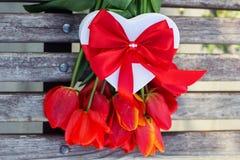 Fleurs et boîte-cadeau rouges de tulipe sur la table en bois Image stock
