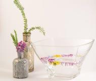 Fleurs et bouteilles de flottement Photographie stock