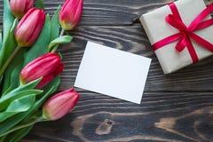 Fleurs et cadeau rouges de tulipe avec le ruban et la carte de voeux rouges dessus Photos stock
