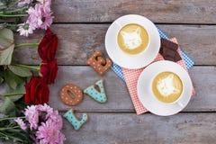 Fleurs et cappuccino, vieux fond en bois Image stock