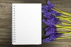 Fleurs et carnet vide sur une table en bois foncée Photographie stock