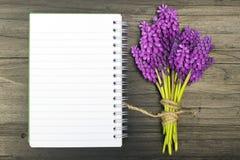 Fleurs et carnet vide sur une table en bois foncée Photos libres de droits