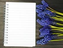 Fleurs et carnet vide sur une table en bois foncée Images libres de droits