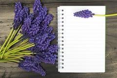 Fleurs et carnet vide sur une table en bois foncée Photo libre de droits