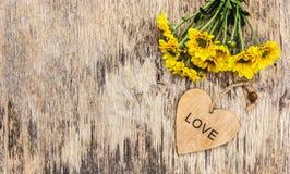 Fleurs et coeur jaunes d'été sur un fond en bois Copiez l'espace Images libres de droits