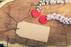 Fleurs et coeur sur le bois avec l'étiquette photographie stock