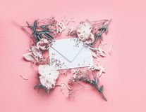 Fleurs et disposition de pétale autour d'enveloppe vide sur le fond rose avec des rubans, vue supérieure Lettre de sentiment d'am image libre de droits