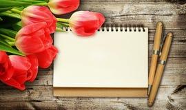 Fleurs et note de tulipe sur le fond en bois foncé Images stock