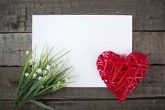 Fleurs et papier de note de forme de coeur sur le fond en bois Images libres de droits