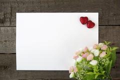 Fleurs et papier de note de forme de coeur sur le fond en bois Photographie stock