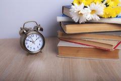 Fleurs et réveil de livres image stock