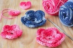 Fleurs faites main et coeur roses et bleus de crochet Photographie stock libre de droits
