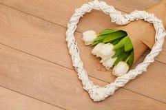 Fleurs fraîches de tulipes et coeur décoratif sur les planches en bois Photos libres de droits