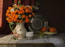 Fleurs, fruit et tasse de thé Photo stock