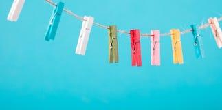 Fleurs goupillées sur la corde à linge Fond de minimalisme Fond bleu, orange, gris Photo de haute résolution Images stock