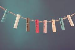 Fleurs goupillées sur la corde à linge Fond de minimalisme Fond bleu, orange, gris Photo de haute résolution Images libres de droits