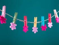 Fleurs goupillées sur la corde à linge Fond de minimalisme Fond bleu, orange, gris Photo de haute résolution Image stock