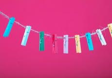 Fleurs goupillées sur la corde à linge Fond de minimalisme Fond bleu, orange, gris Photo de haute résolution Photo libre de droits
